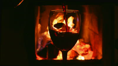 stock-footage-glass-of-wine-on-a-background-of-fire